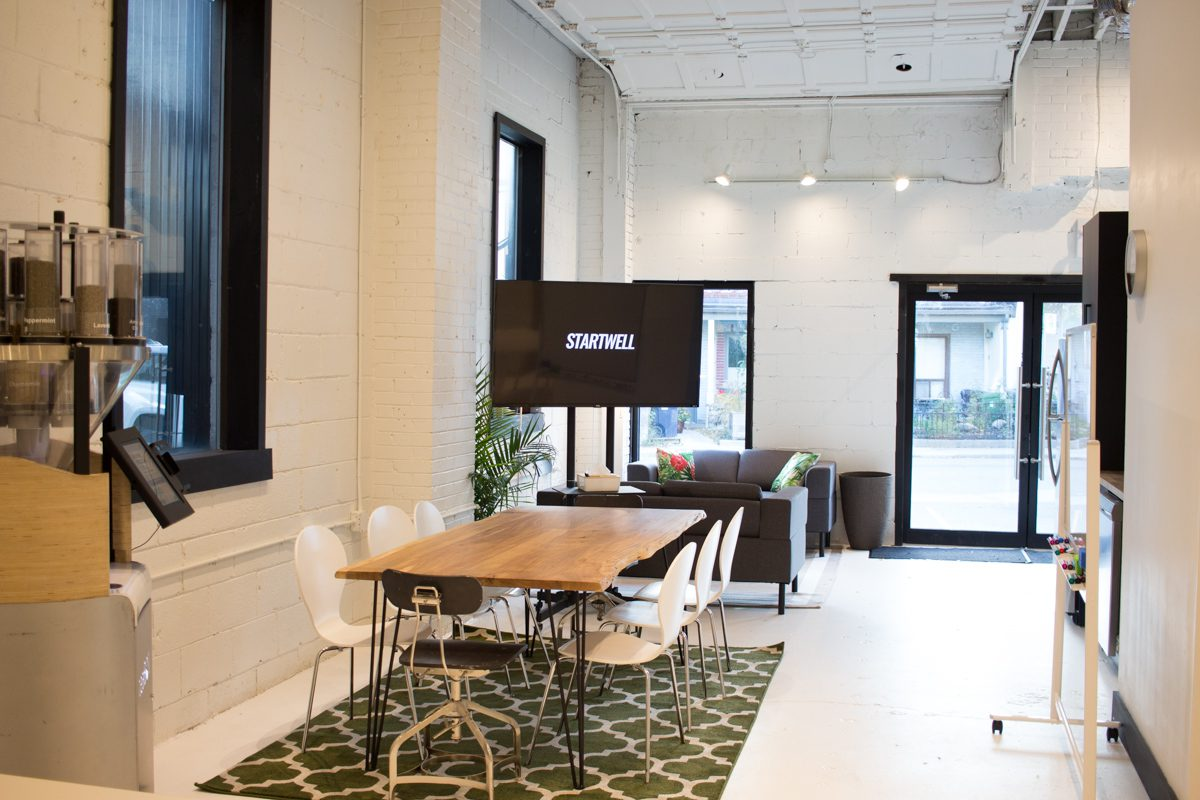 The entrance at StartWell property 230 Niagara, which features local startup teaBot in the open kitchen experience. https://teabot.com/ and the original garage door from when the building was a mechanic's garage.