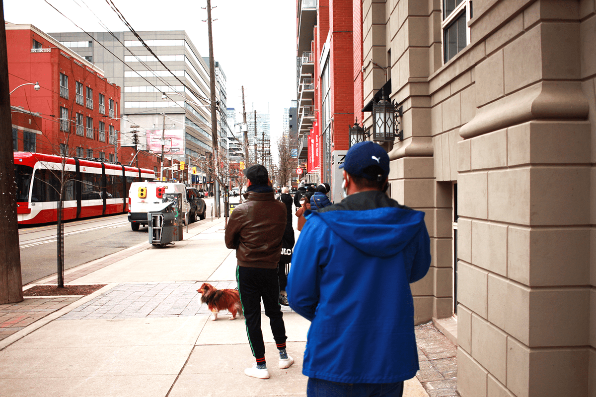 People line up, distanced from each other waiting to get into a drugstore across from StartWell on King St W in Toronto